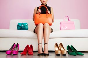 Woman sitting on sofa with colorful shoes and bags. Shopping.